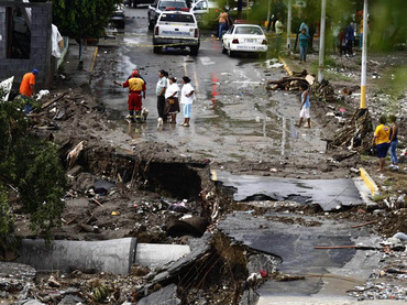 Residents stand near a bridge damaged by floodwaters from La Silla river in the aftermath of Hurricane Alex at El Realito neighbourhoood in the suburb of Guadalupe, neighbouring Monterrey July 6, 2010. Tens of thousands of residents were without water and electricity and more than 4,000 people were moved to shelters in Mexico's richest city 140 miles (230 km) south of McAllen, Texas. REUTERS/Tomas Bravo (MEXICO - Tags: ENVIRONMENT DISASTER) STORM-ALEX/MONTERREY MEX55_STORM-ALEX-MONTERREY_0706_11.JPG