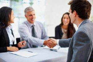 Young business man shaking hands with senior manager in the office